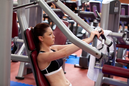 Attractive athletic woman using a bench press photo
