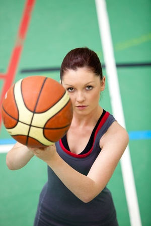 Portrait of a concentrated young woman playing basket-ball photo