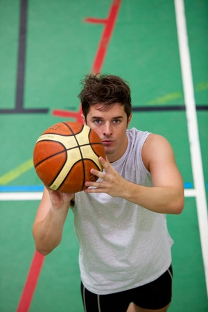 Portrait of a muscular young man playing basket-ball photo