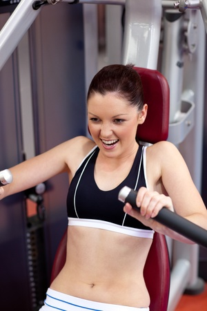 musculation: Charming athletic woman using a bench press