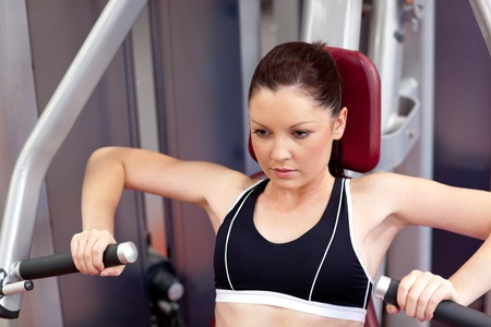 musculation: Concentrated athletic woman using a bench press