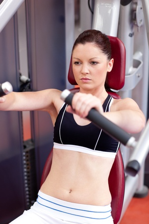 musculation: Positive athletic woman using a bench press