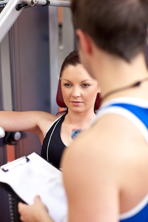 Assertive athletic woman using a bench press with her coach Stock Photo - 10242728