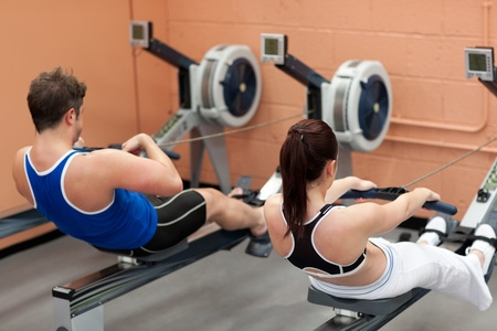 concentrated: Concentrated people using a rower Stock Photo