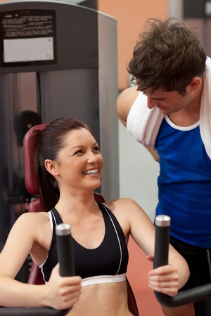 musculation: Joyful athletic woman using a shoulder press with her coach