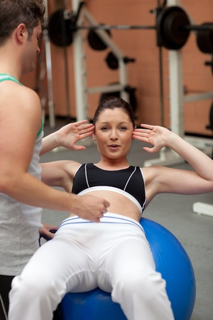 musculation: Athletic young woman sitting on a musculation ball with her coach