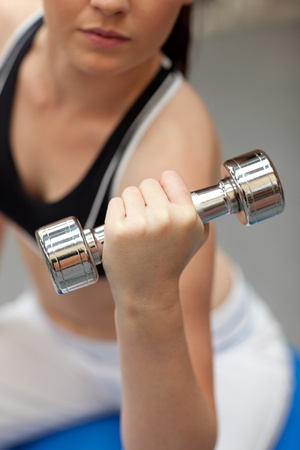 musculation: Portrait of a cute woman working out with dumbbells