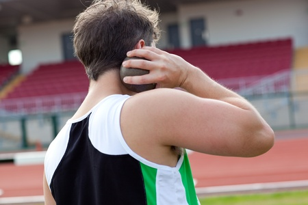 Concentrated male athlete preparing to throw weight Stock Photo - 10242725