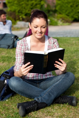 Young female student reading a book sitting on grass photo