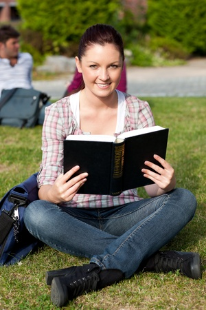 Serious female student reading a book sitting on grass photo