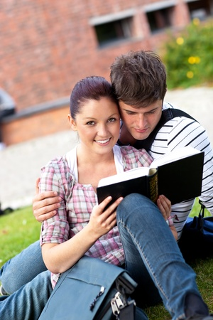 Young couple of students reading a book sitting on grass photo