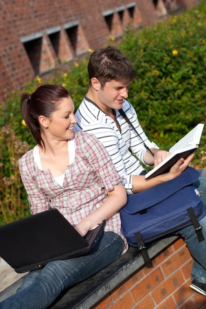 Young couple of students reading a book and using a laptop photo
