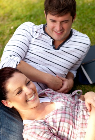 Positive couple of students sitting on grass and smiling at the camera Stock Photo - 10242977
