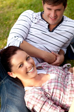 Joyful couple of students sitting on grass and smiling at the camera Stock Photo - 10243380