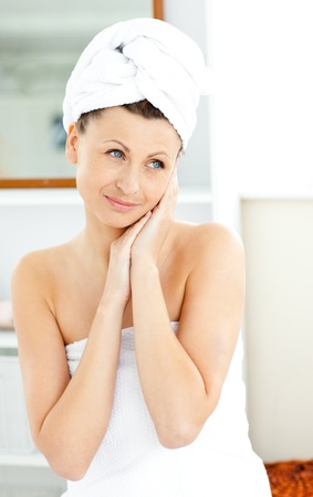 Charming young woman with a towel putting cream on her face in the bathroom photo