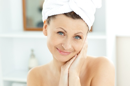 Attractive young woman with a towel putting cream on her face in the bathroom photo