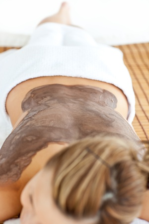 Young caucasian woman lying on a massage table with mud on her back