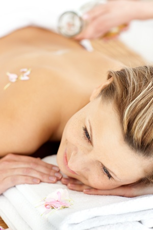 elated: Pretty young woman enjoying a back massage with oil