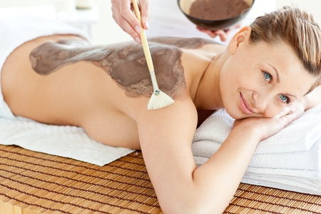 Merry caucasian woman receiving a beauty treatment with mud photo