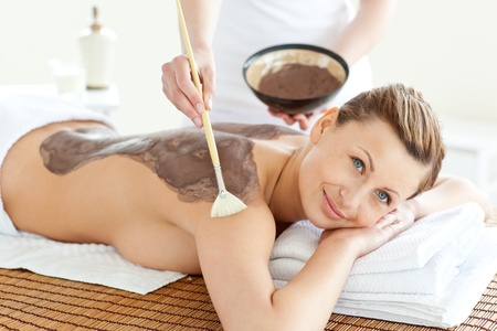 Delighted caucasian woman receiving a beauty treatment with mud photo