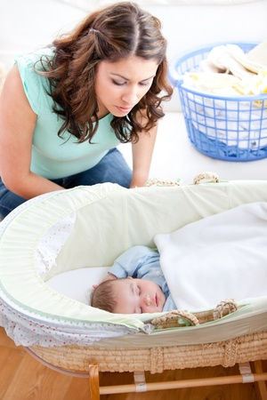 lookalike: Young mother looking at her little son sleeping in his bed