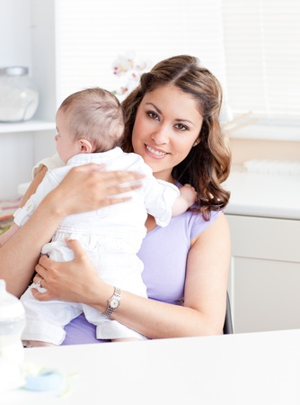 Positive young mother holding her baby in the kitchen photo
