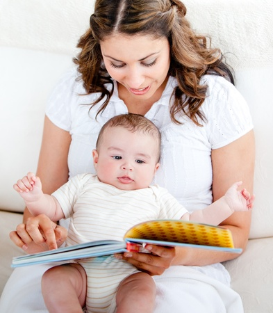 lookalike: Loving mother reading a story to her adorable baby sitting on the sofa