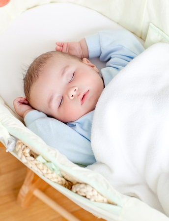 Adorable baby sleeping in his bed photo