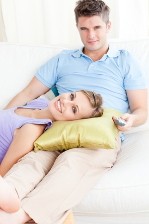 Affectionate couple watching television on the sofa in the living-room photo