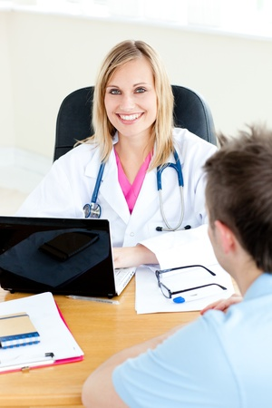 Smiling female doctor using her laptop and talking to her male patient photo