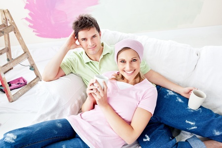 paintrush: Delighted couple lying on the sofa after painting their new room Stock Photo