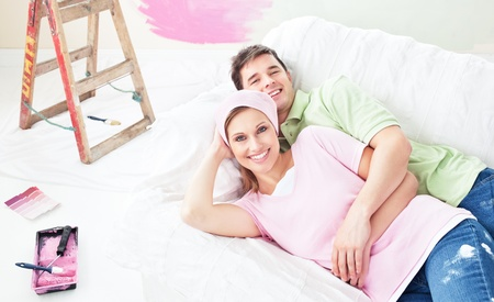 Positive couple lying on a sofa after painting a room Stock Photo - 10242709