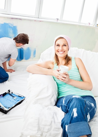paintrush: Smiling woman relaxing on a sofa while boyfriend painting the room Stock Photo