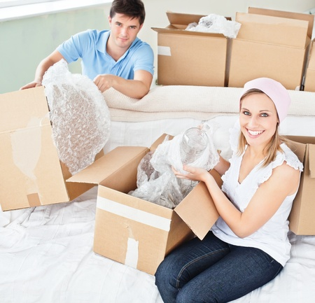 Merry young couple unpacking boxes with glasses photo