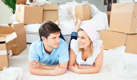 Young couple lying on the floor after unpacking boxes Stock Photo - 10243443
