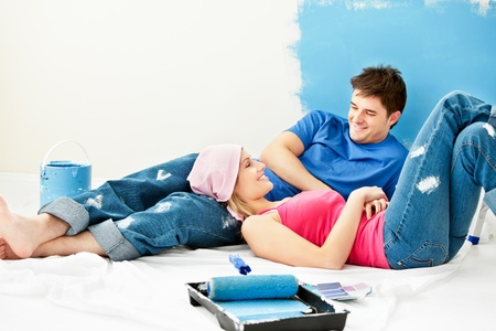 Happy couple relaxing after painting a room photo