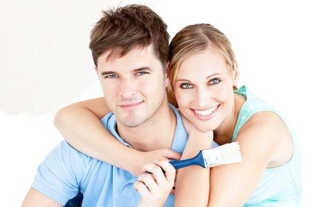 paintrush: Smiling caucasian couple painting a room