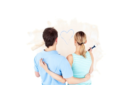 Kind young couple painting a room photo