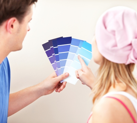 Concentrated couple choosing color for a room in their new house photo