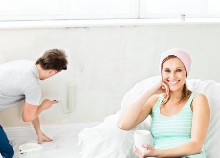 paintrush: Smiling caucasian woman relaxing on a sofa while boyfriend painting the room