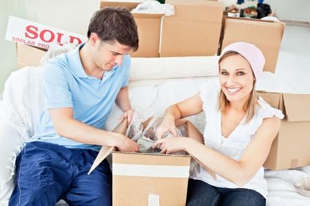 Joyful caucasian couple unpacking boxes with glasses Stock Photo - 10243377
