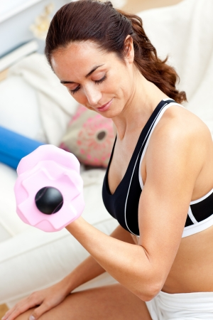 Young athletic woman holding a dumbbell in her living-room Stock Photo - 10242799