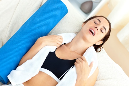 Exhausted woman sitting on a sofa after working out in her living-room Stock Photo - 10242798