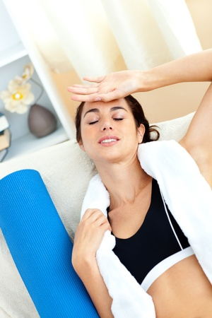 Tired woman sitting on a sofa after working out in her living-room Stock Photo - 10242527
