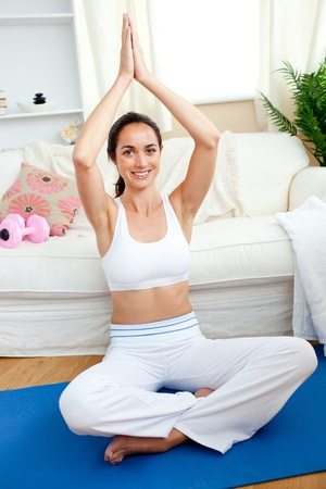 Smiling woman practicing yoga in her living-room photo