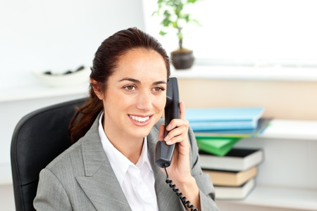 Attractive businesswoman talking on phone sitting in her office photo