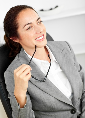 assertive: Assertive businesswoman holding her glasses sitting in her office