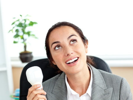 Surprised businesswoman holding a light bulb sitting in her office photo