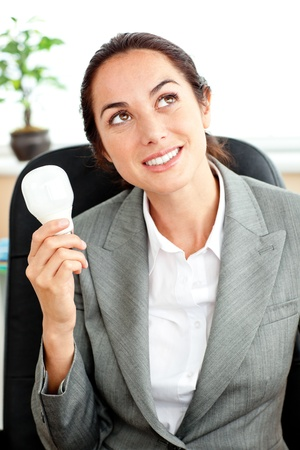 Thoughtful businesswoman holding a light bulb in her hand sitting at her desk photo