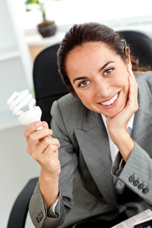 Beautiful businesswoman holding a light bulb in her hand sitting at her desk photo